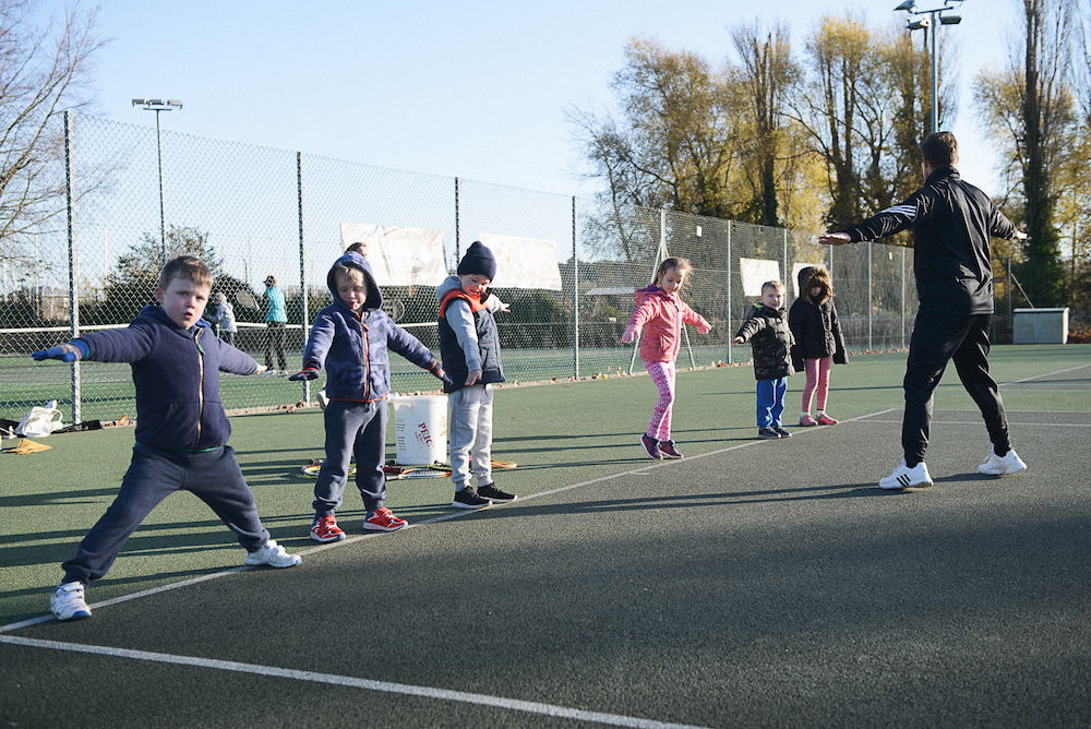 Warm up on court at Mini Red tennis session
